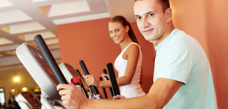 A young couple working out on an elliptical cross trainer