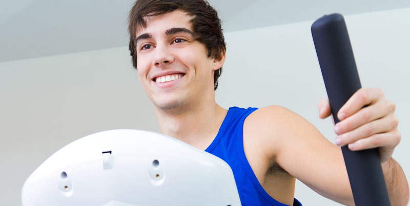 A man smiling while working out on a cross trainer