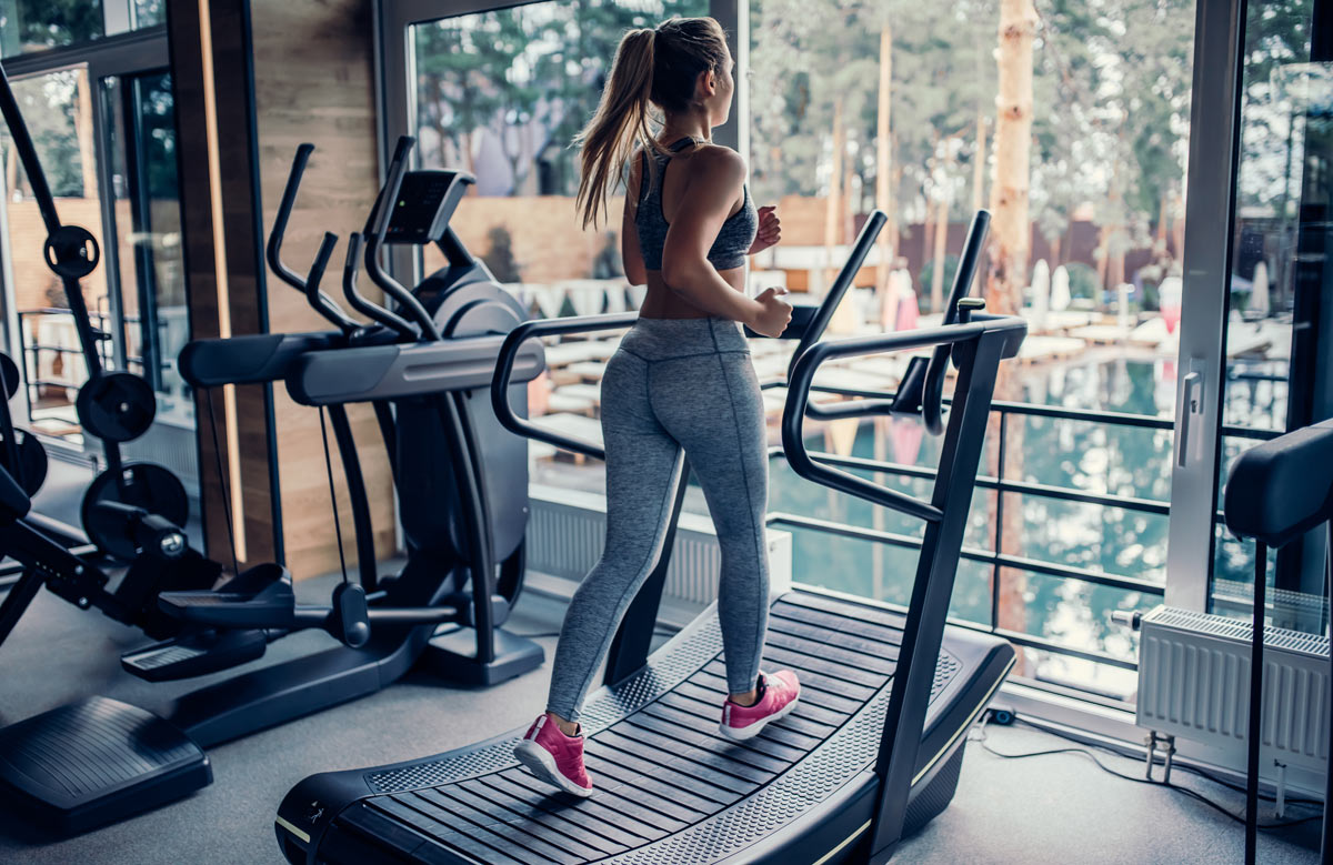 A woman running on a curved belt manual treadmill